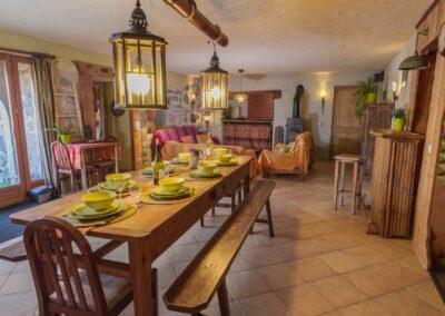 La salle à manger et le salon du gîte avec la table prête pour 8 personnes.